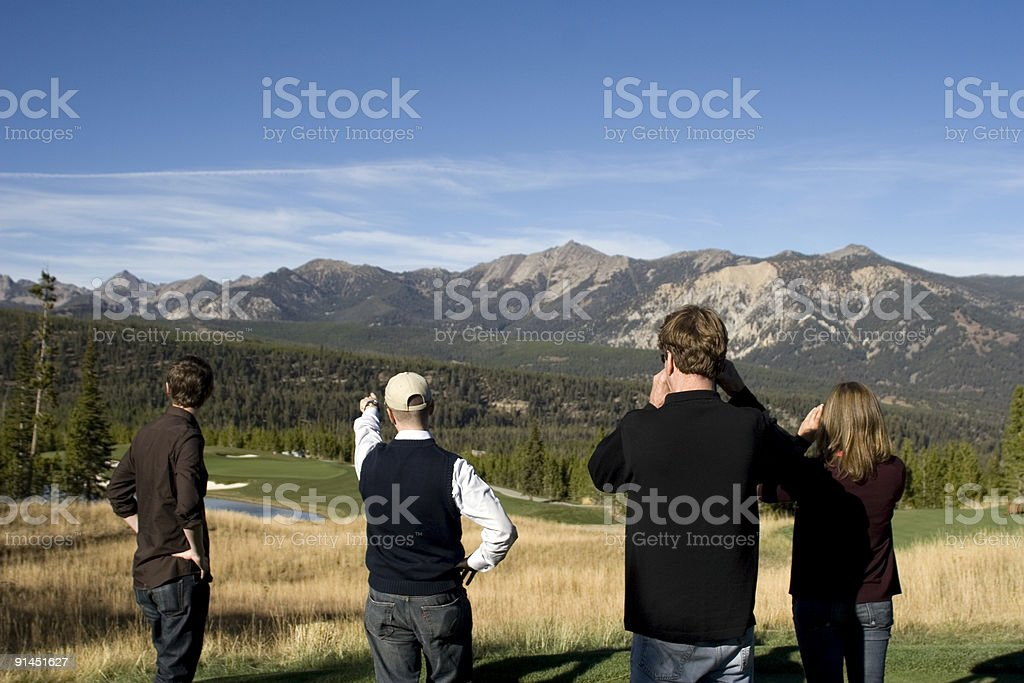 Group surveying golf course in mountain region royalty-free stock photo