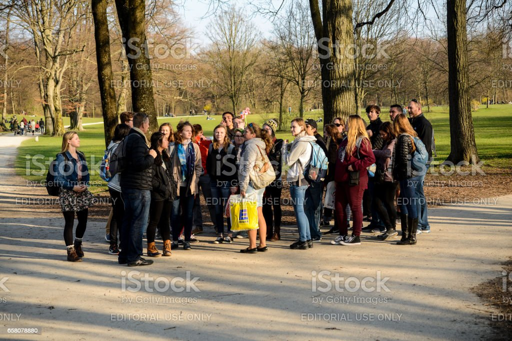 A group tourists takes a guided tour of the Englischer Garten stock photo
