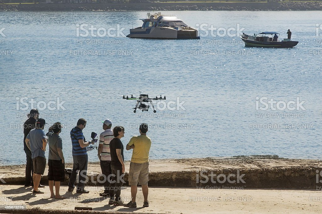 Group watches a quadcopter flying stock photo