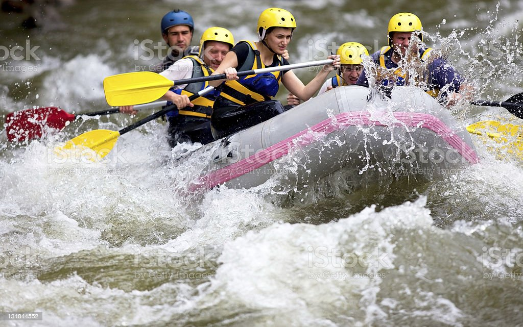 Group whitewater rafting down rough river stock photo