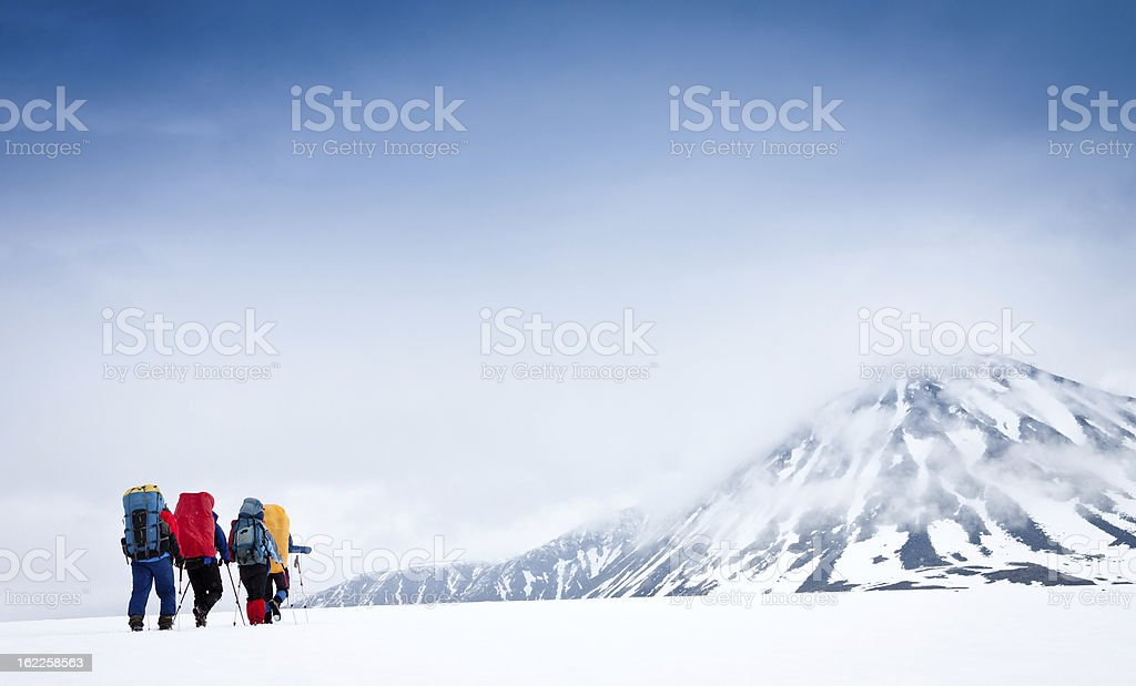 Group with gear and backpacks crossing icy field to mountain royalty-free stock photo