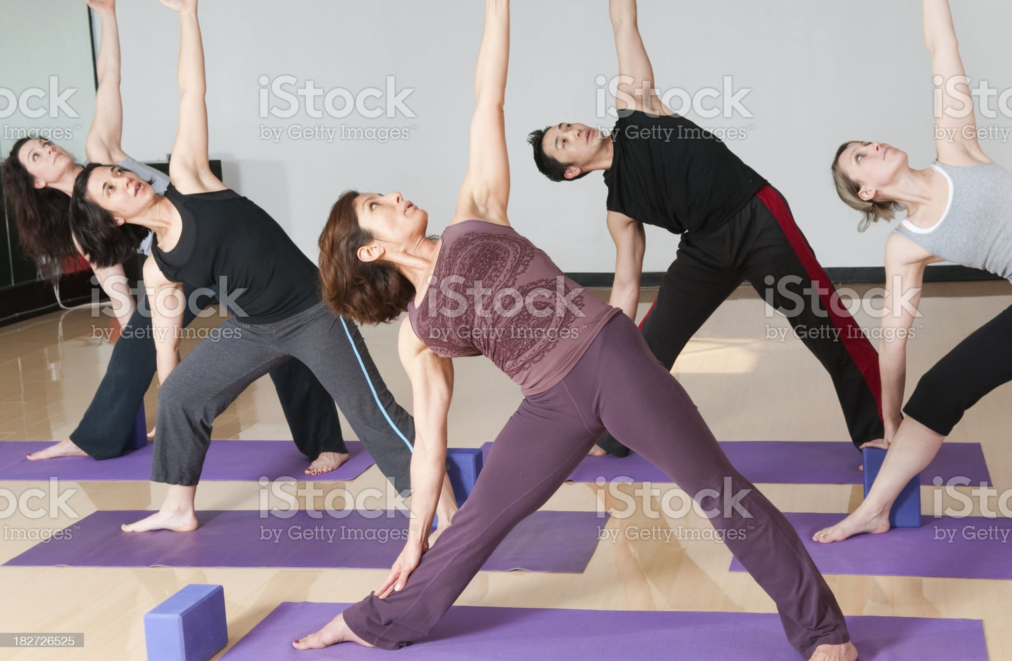Group Yoga Class Doing Extended Triangle Pose royalty-free stock photo