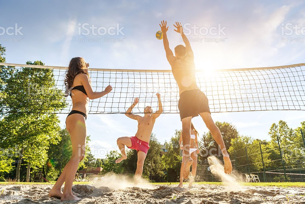 Group young  Friends Playing Volleyball On Beach stock photo