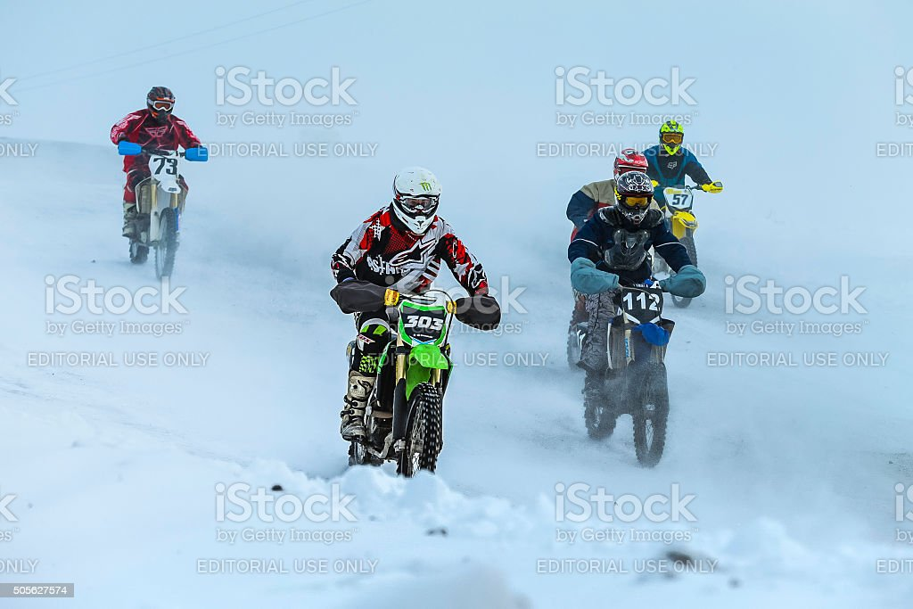 group young racers drive on snowy motocross track stock photo