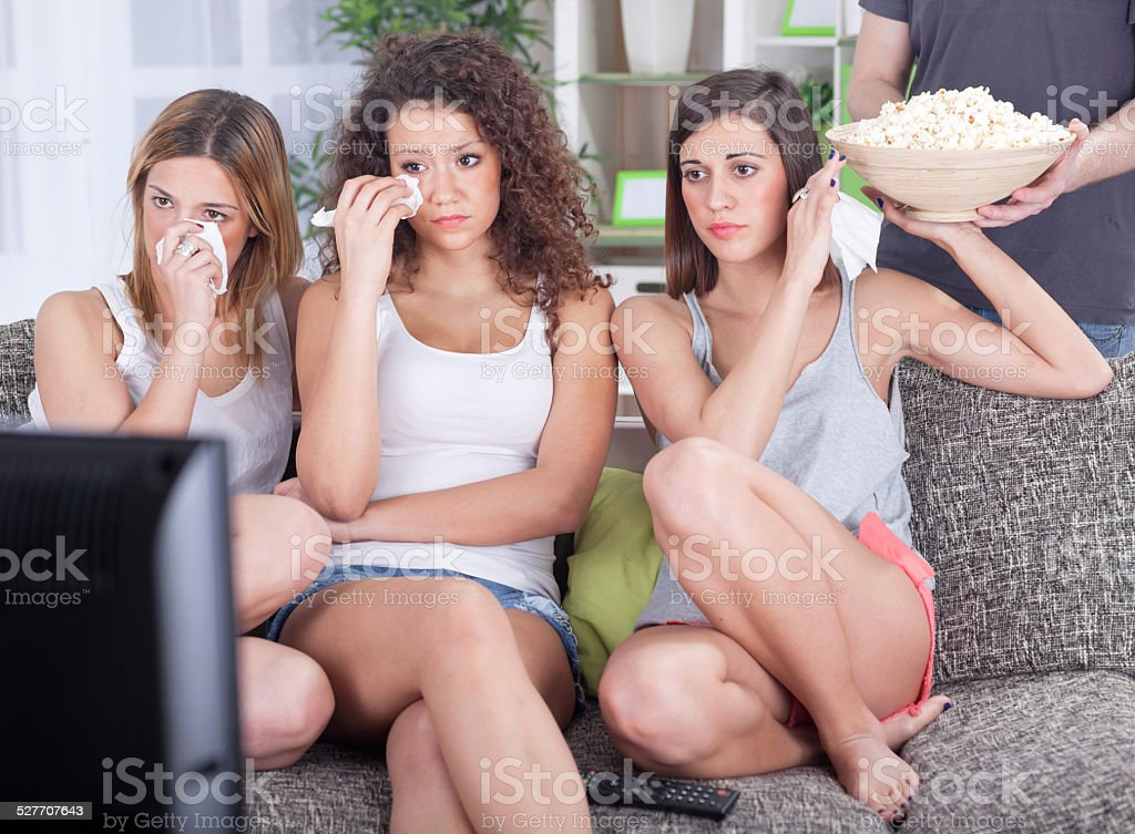 group  young women sitting on couch watching sad movie depress stock photo