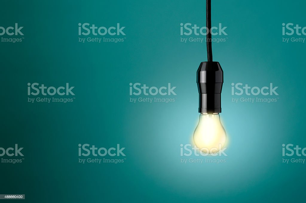 Growing light bulb against blue background with copy space stock photo