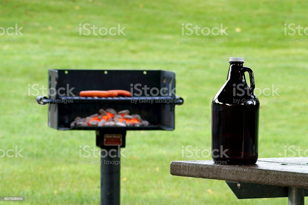 Growler in Front of Charcoal Grill stock photo