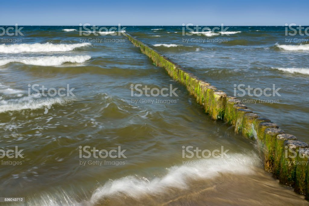 Groynes and waves at the sea stock photo