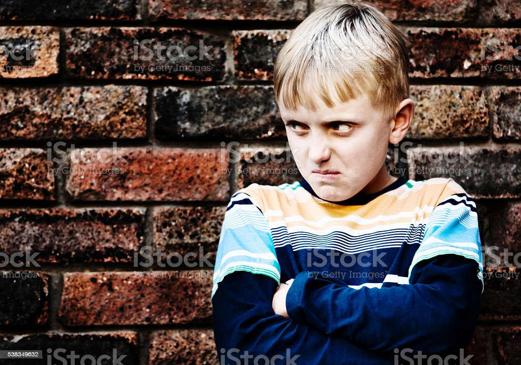 Grumpy, 10 years boy, scowling, angry, aggressive, unhappy, copy space stock photo