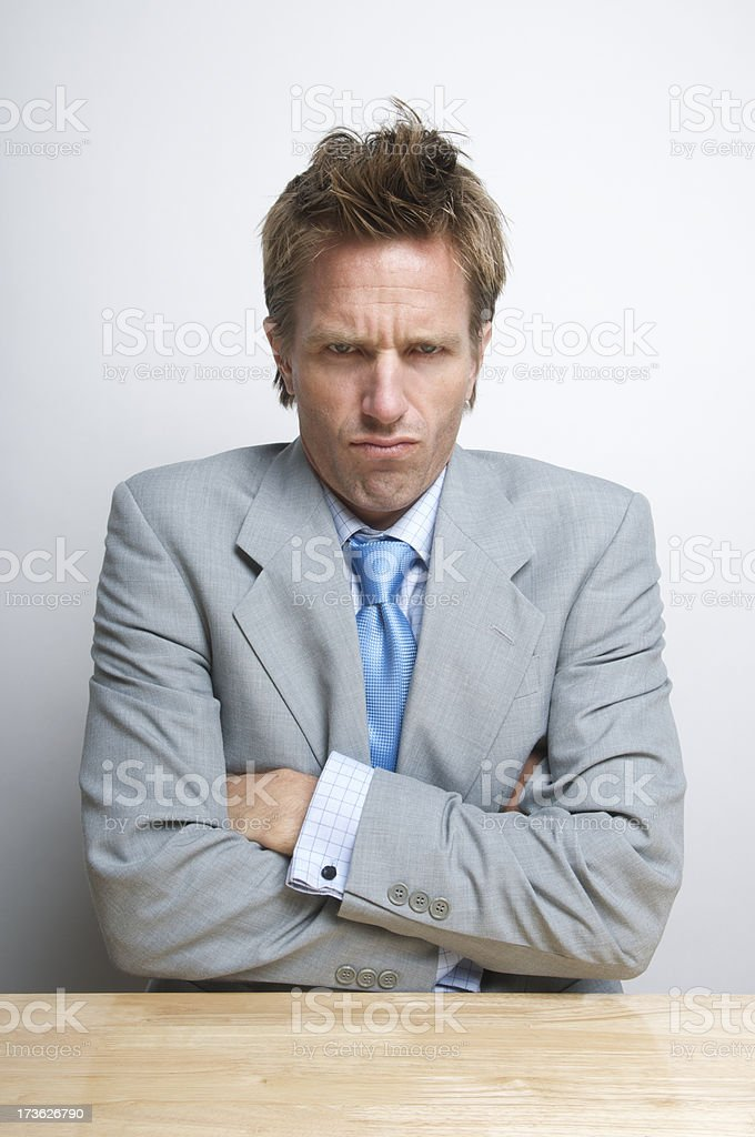 Grumpy Businessman Folds Arms at Desk royalty-free stock photo
