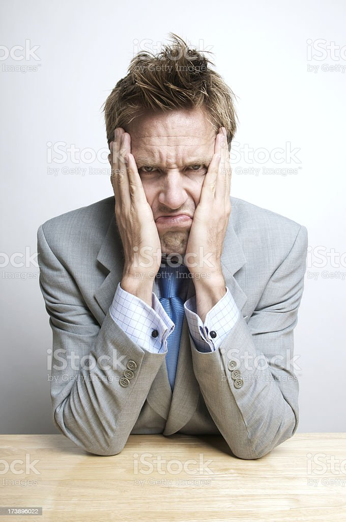 Grumpy Businessman Sitting Pouting at his Desk royalty-free stock photo