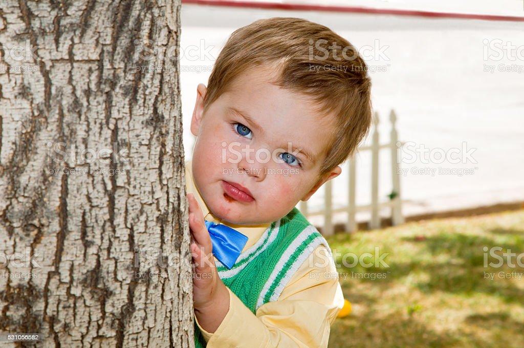 Grumpy Face Boy Peeks Around Tree stock photo