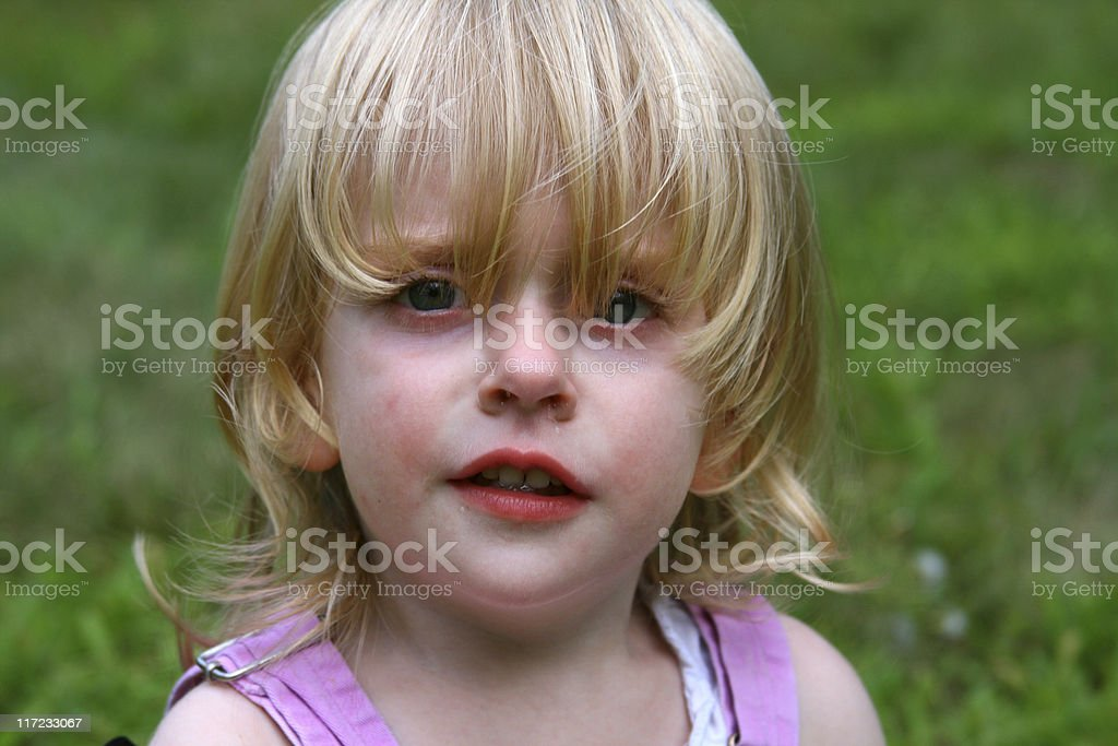 Grumpy Girl: Pouting unhappy toddler in pink overalls stock photo