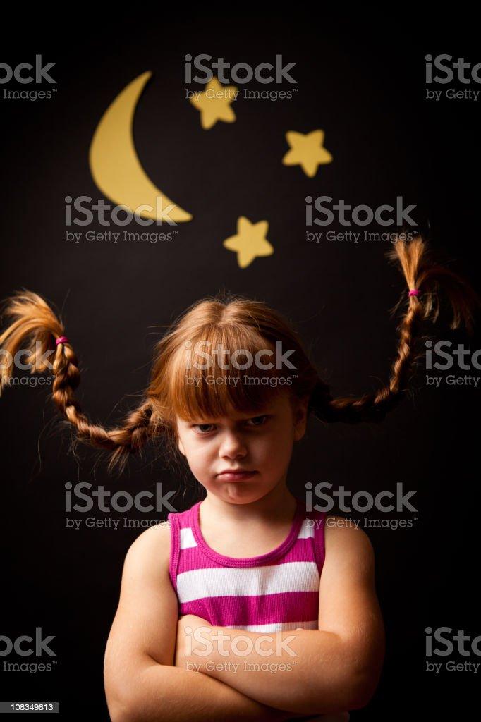 Grumpy Girl with Upward Braids Standing Under Moon and Stars stock photo