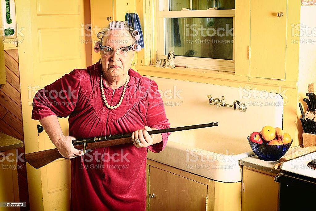 Grumpy Granny in Kitchen with Gun stock photo