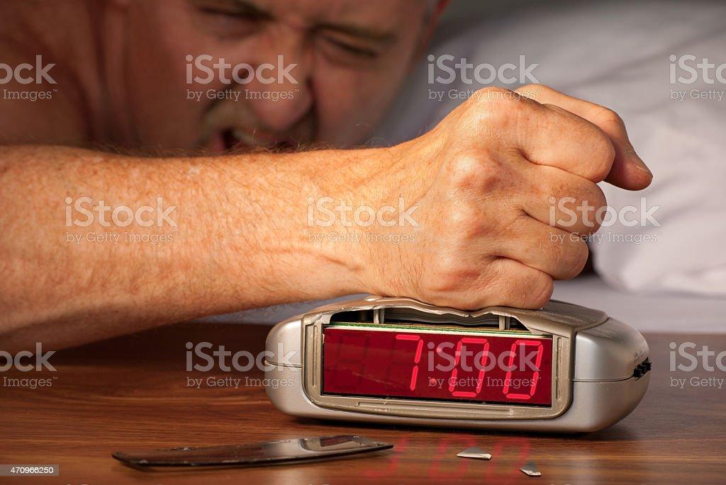 Grumpy hung over man mashing alarm clock at 7:00 a.m. stock photo