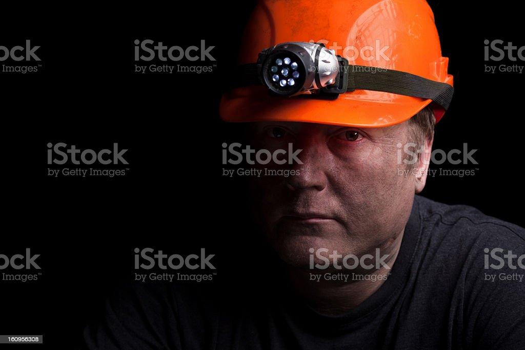 Grumpy looking miner in an orange safety hat stock photo