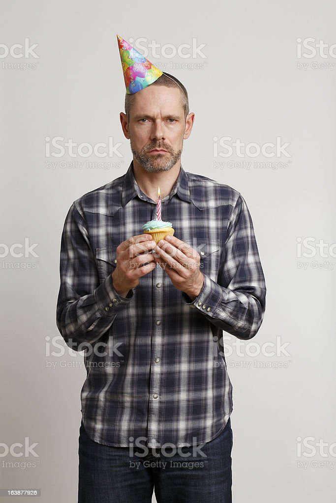 Grumpy Man in Party Hat Holding Cupcake With One Candle royalty-free stock photo