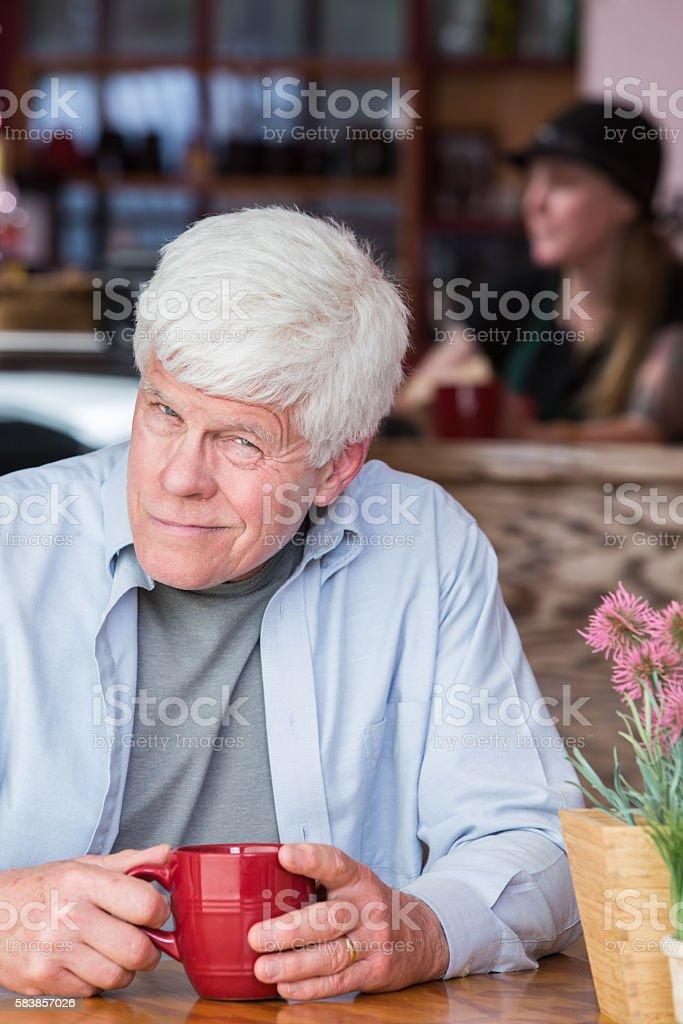 Grumpy Mature Man in Coffee House stock photo
