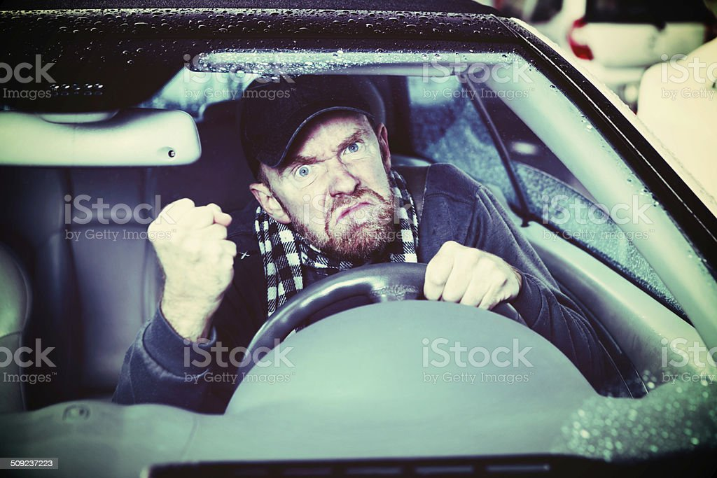 Grumpy old man! Angry driver shakes his fist stock photo
