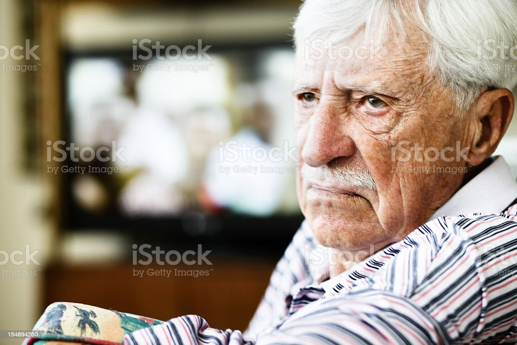 Grumpy old man looks round from television, frowning stock photo