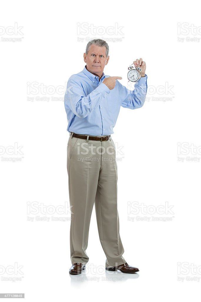 Grumpy old man pointing to his alarm clock on white royalty-free stock photo
