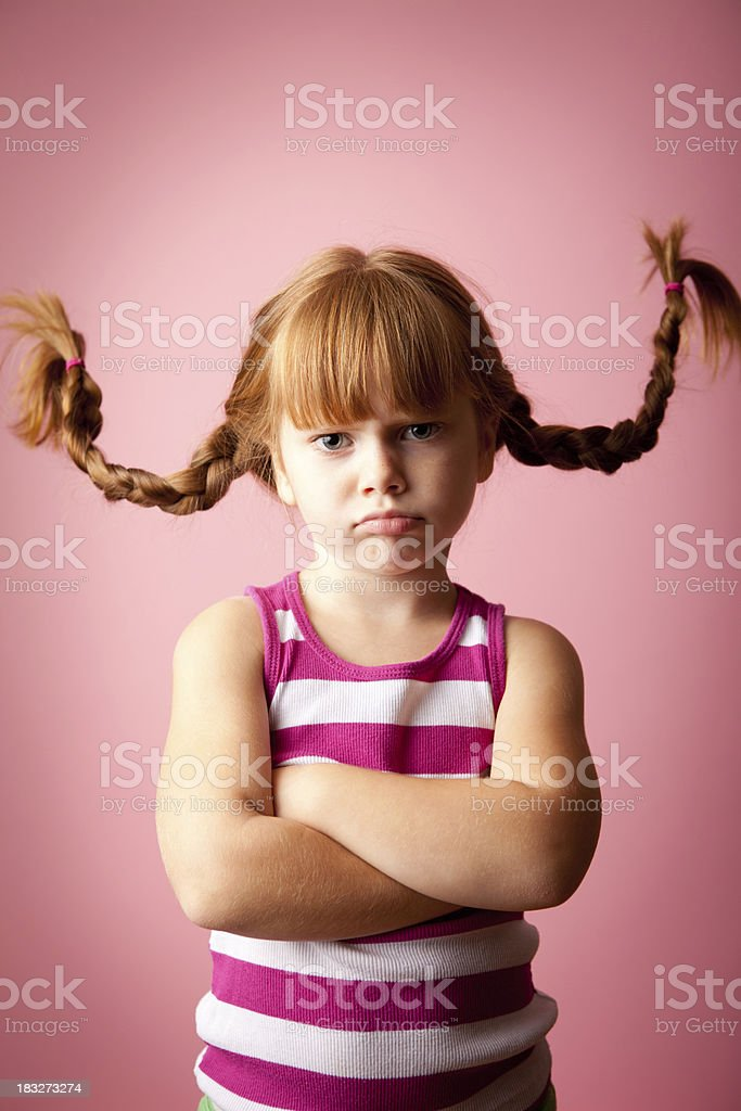 'Grumpy Red-Haired Girl Standing with Upward Braids, Arms Crossed' stock photo