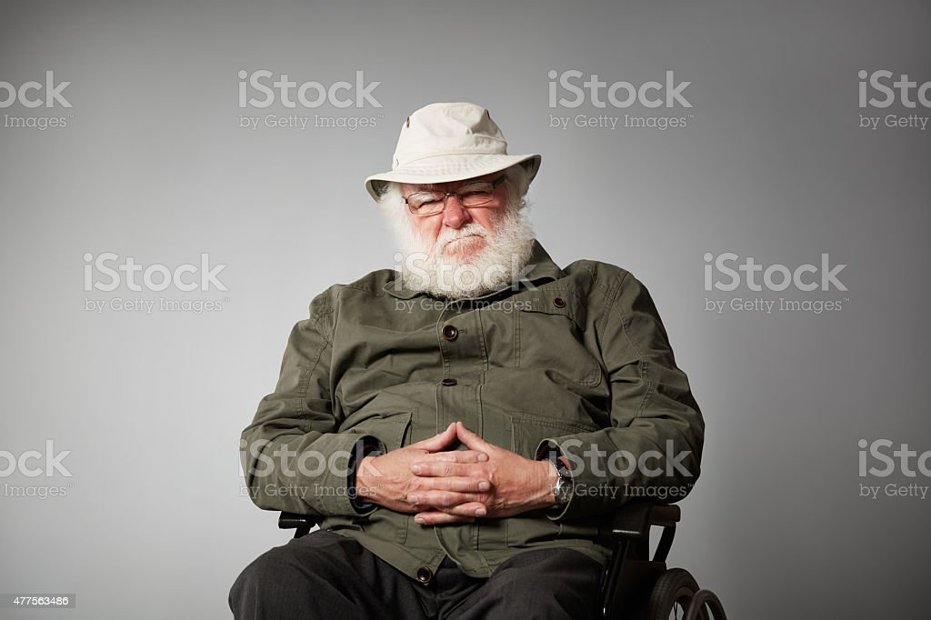 Grumpy senior man on wheelchair stock photo