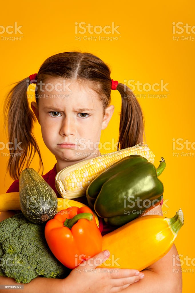 Grumpy Young Girl Holding Bell Peppers, Broccoli, Squash, Zucchini royalty-free stock photo