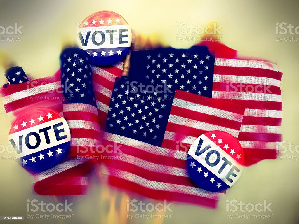 Grunge and blurred American flags with VOTE campaigns buttons stock photo