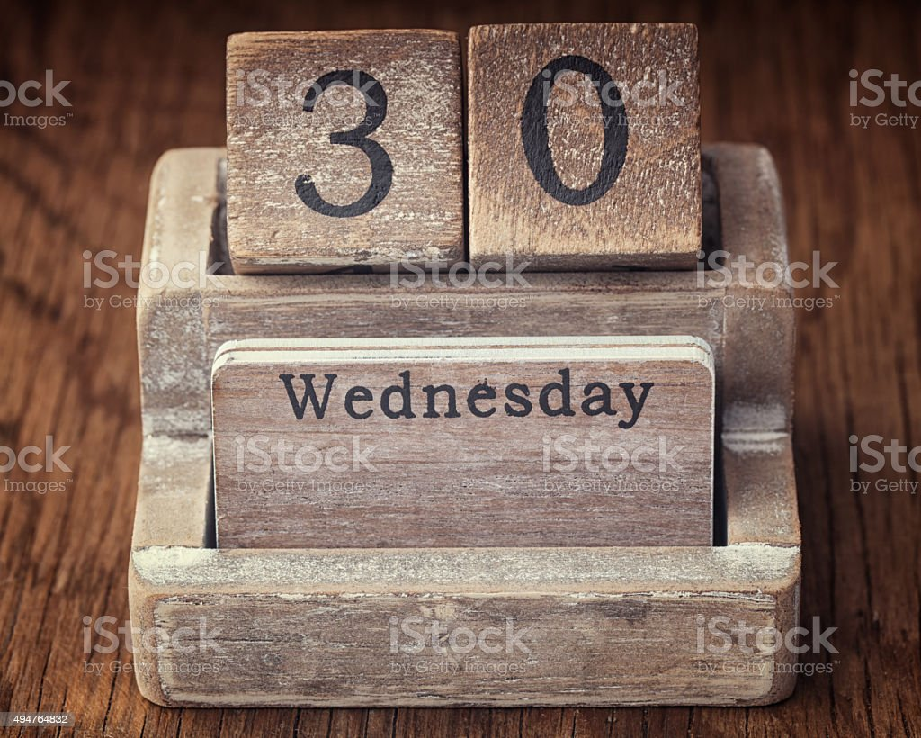 Grunge calendar showing Wednesday the thirtieth on wood backgrou stock photo