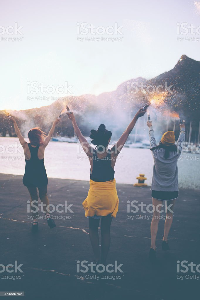 Grunge girls holding flares at the harbour in the evening stock photo