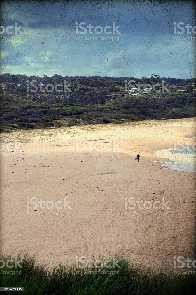 Grunge retro image of deserted beach with lone surfer stock photo
