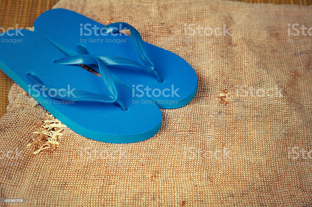 Grunge sacking background with flip flop sandals stock photo