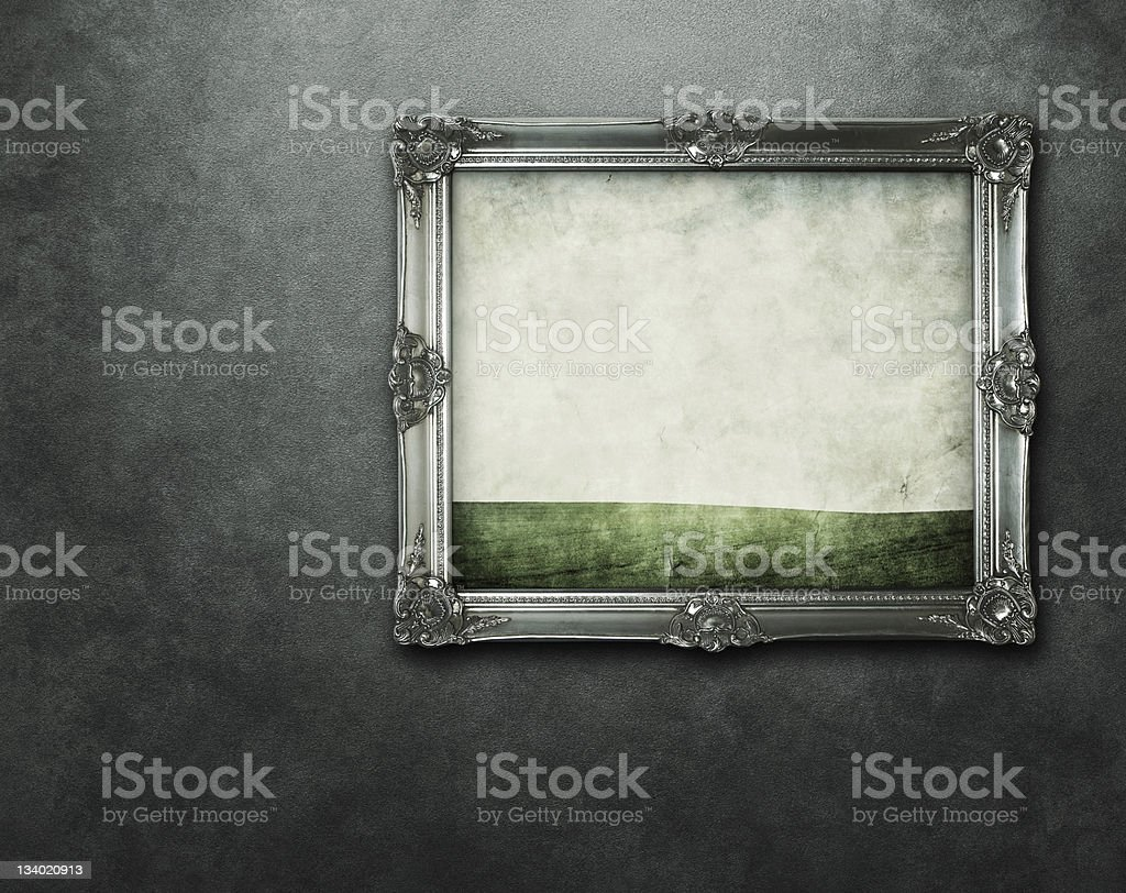 Grunge silver frame hanging at concrete wall with path stock photo