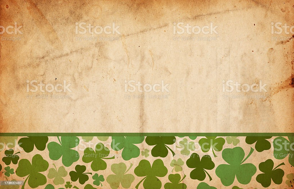 Grunge St. Patrick's Day paper with shamrocks along bottom stock photo