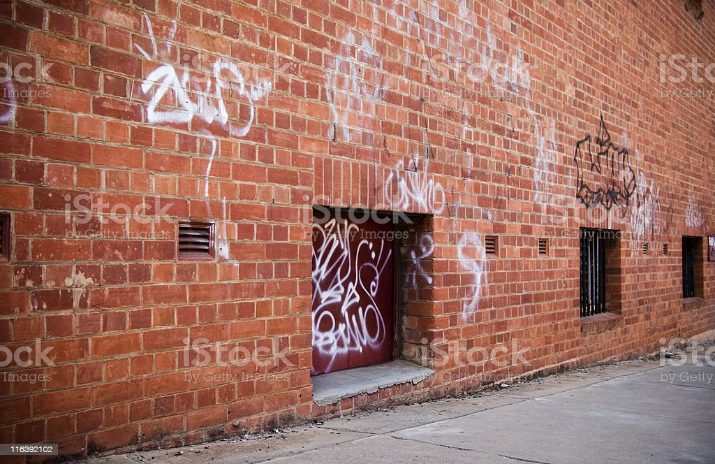 Grunge street scene with red brick wall and graffiti stock photo