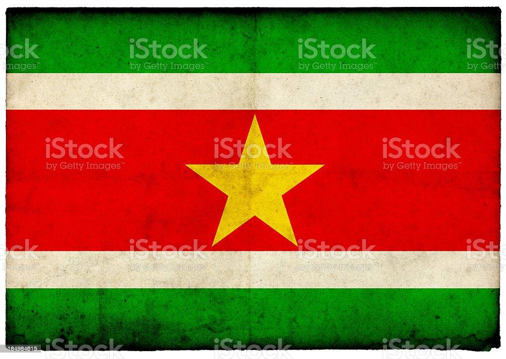 Grunge Suriname Flag on rough edged old postcard stock photo