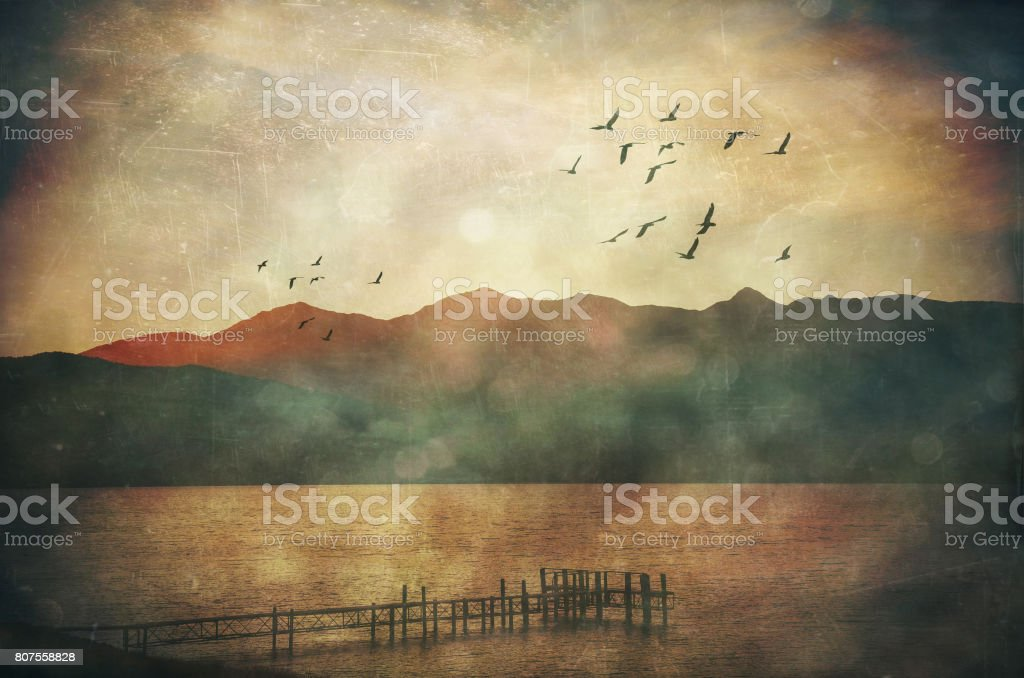 Grunge textured moody landscape of Lake and jetty stock photo