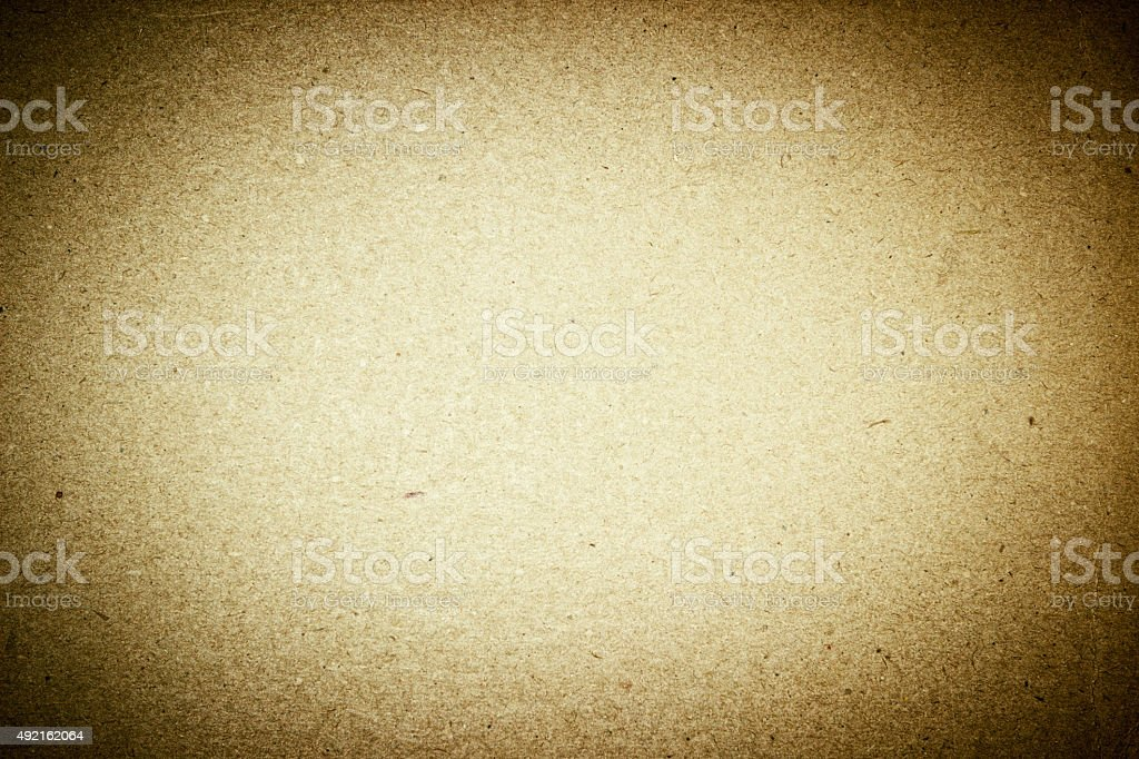 Grunge weathered old paper - golden brown colored and vignetted stock photo