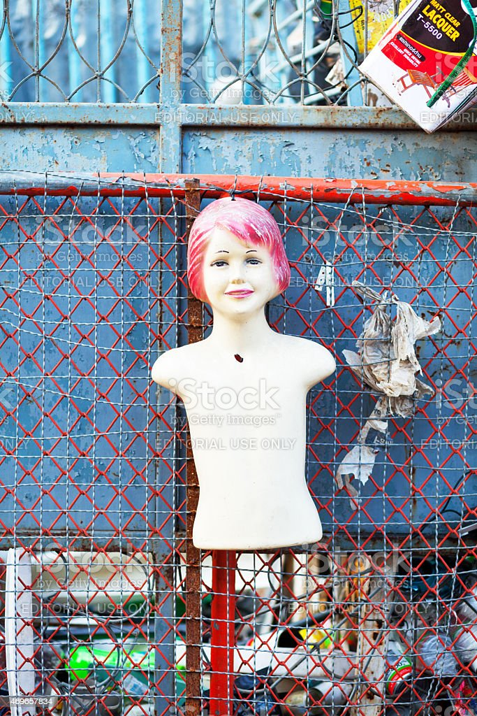 Grunged female body dummy at fence stock photo
