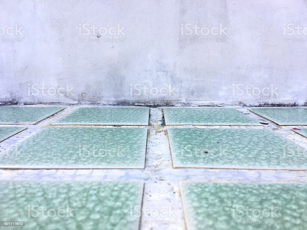 Grungy concrete wall and Green tiled floor room as background royalty-free stock photo