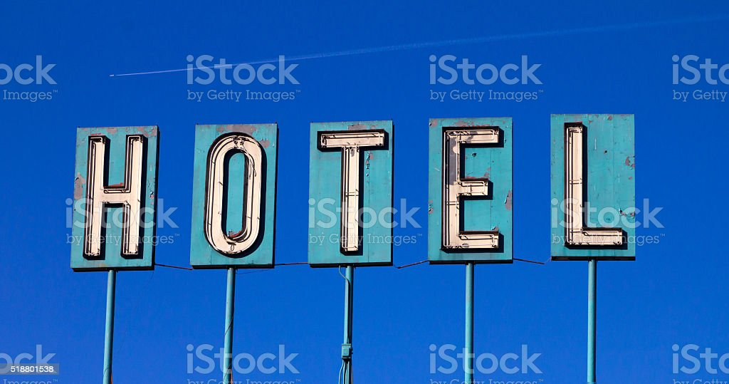 Grungy Old Hotel Sign And Airplane Isolated On Blue stock photo
