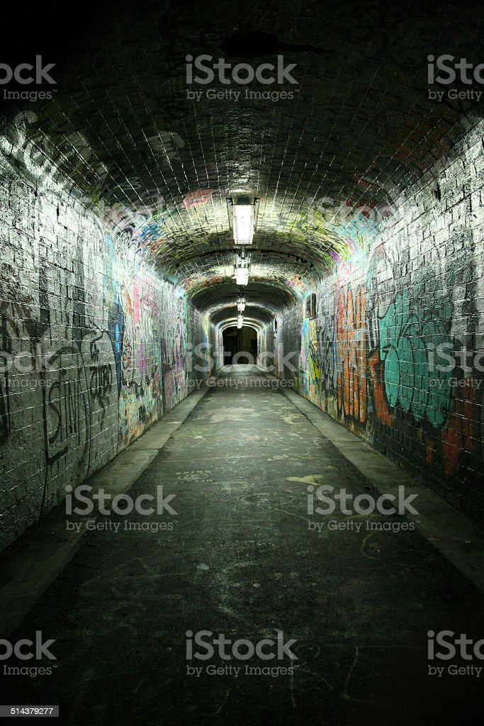 Grungy tunnel with graffitis stock photo