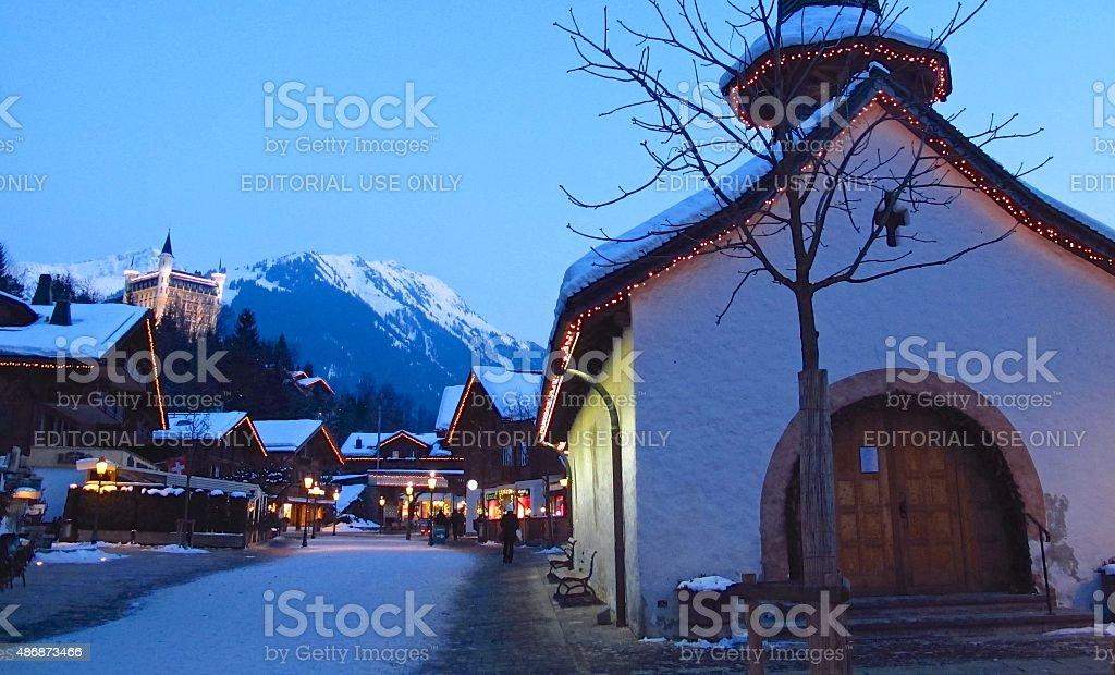 Gstaad Switzerland winter shoppers on snowy street at twilight stock photo