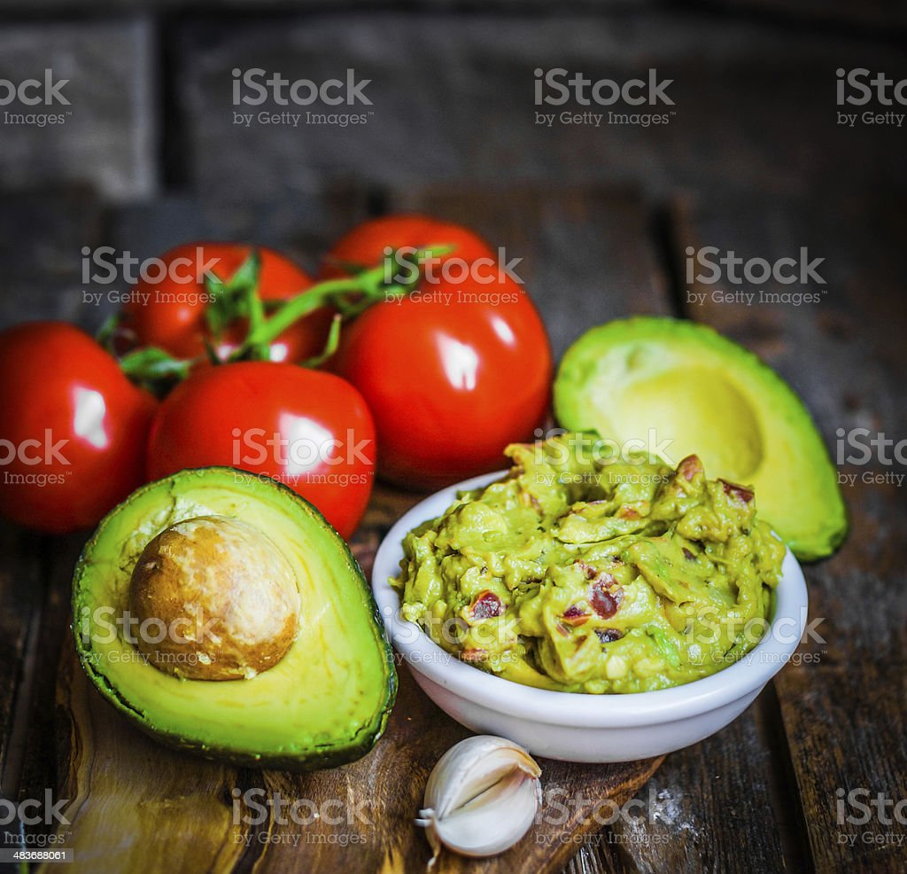 Guacamaole with bread and avocado on rustic wooden background stock photo