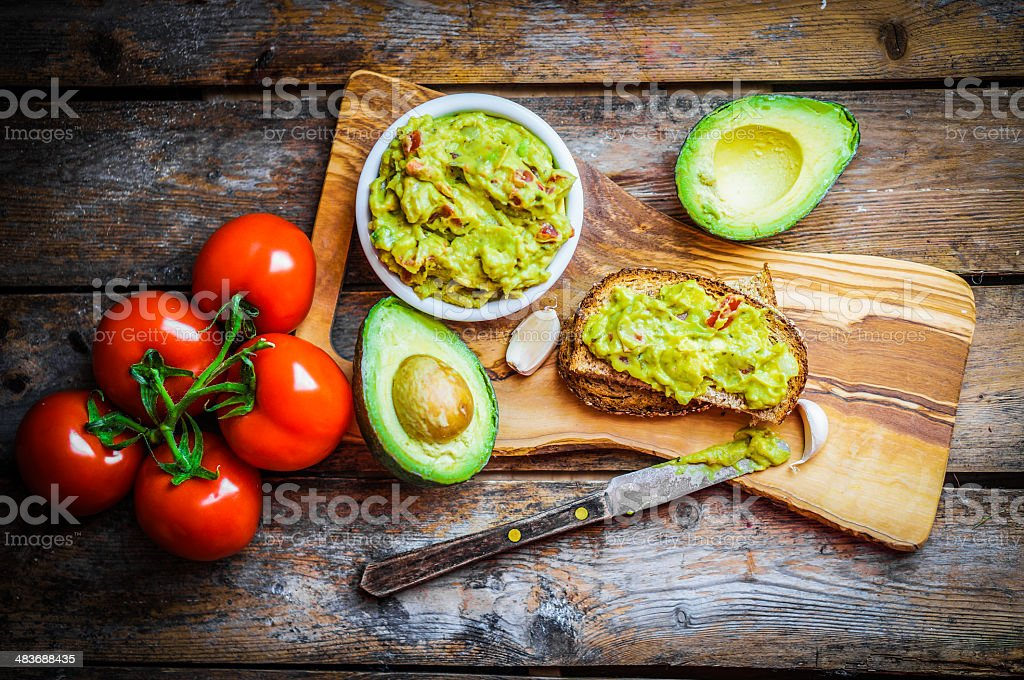 Guacamaole with bread and avocado on rustic wooden background royalty-free stock photo