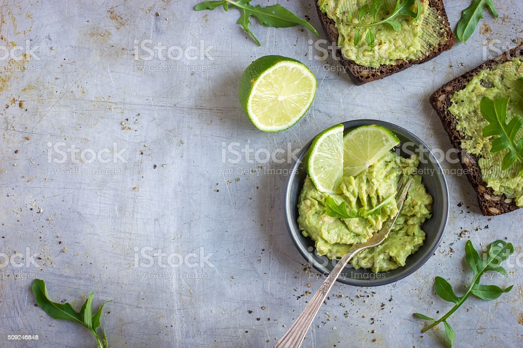 guacamole and rye toasts on rustic  background stock photo