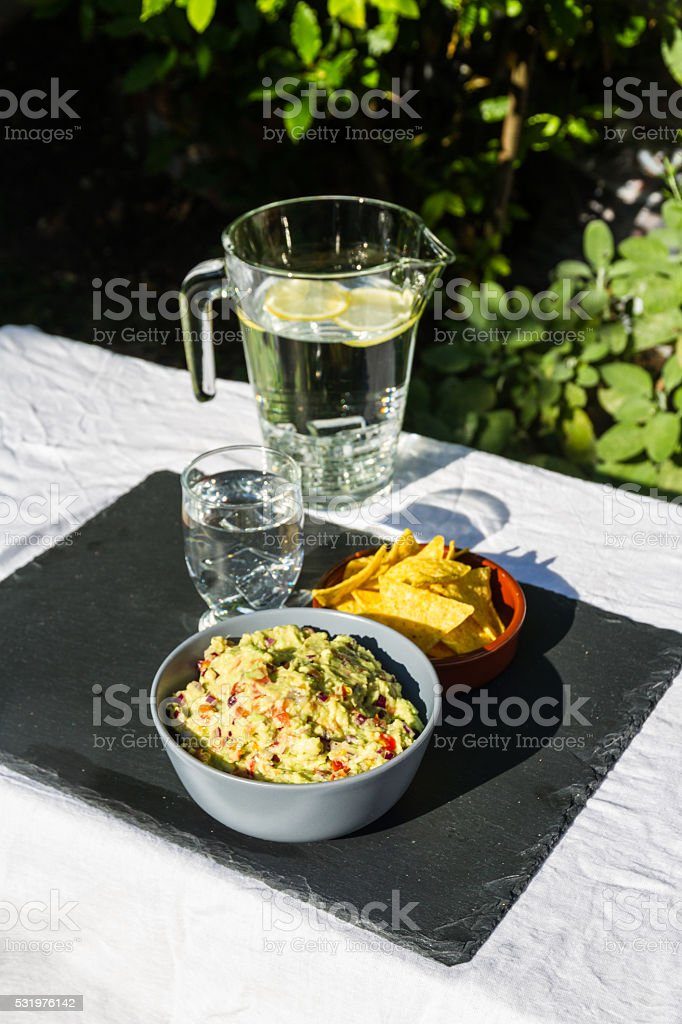 Guacamole in bowl with tortilla chips and iced water. Outdoors stock photo