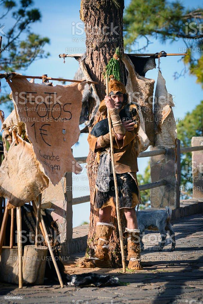 Guanchi aborigine staying near tree stock photo